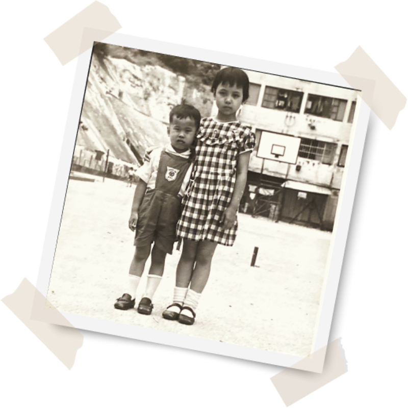 Jenny Seagraves, age 8, with her brother outside her home in Hong Kong.