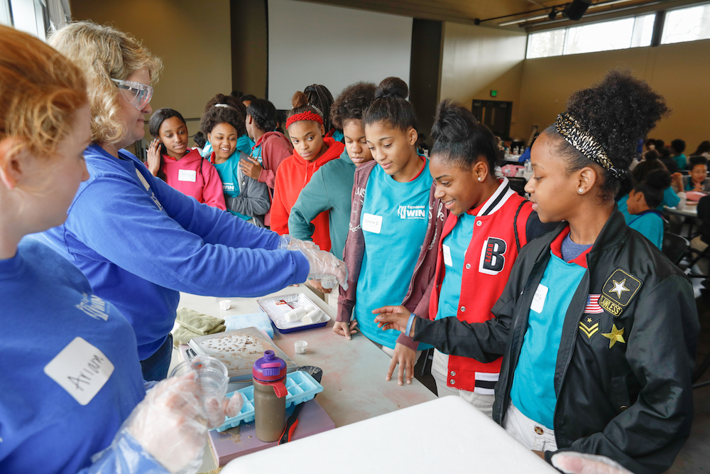 Students at ExxonMobil's Introduce a Girl to Engineering Day work with Dippin' Dots as a part of a science demonstration.